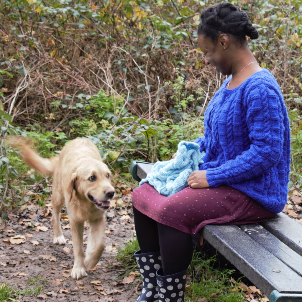 Natalie sitting on a park bench modelling the cornflower blue Reunite cardigan.  She is looking down at a friendly golden retriever, whose tail is wagging.