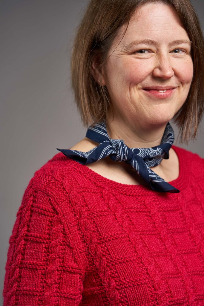 A close-up of Jen modelling the strawberry red Unite sweater with greater focus on the sleeve and shoulder detail.  Image credit: Jesse Wild