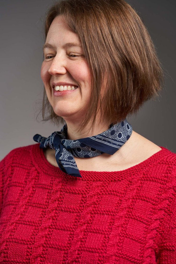 A close-up of the neck detail on the Unite sweater, set off by a navy neck scarf and worn by Jen.  Image credit: Jesse Wild